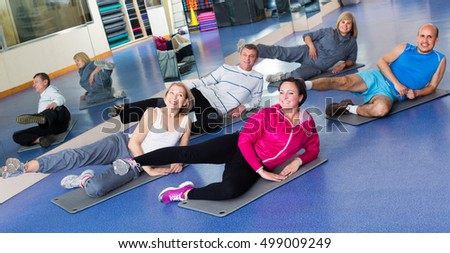 Group of positive active adults doing pilates routine in a sport club