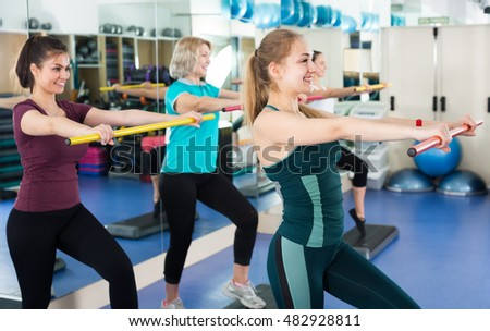 Group of positive cheerful different age women having aerobic train in fitness club. Selective focus
