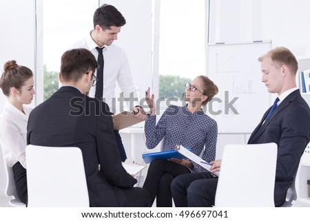 Group of positive corporate workers sitting in a light interior during meeting