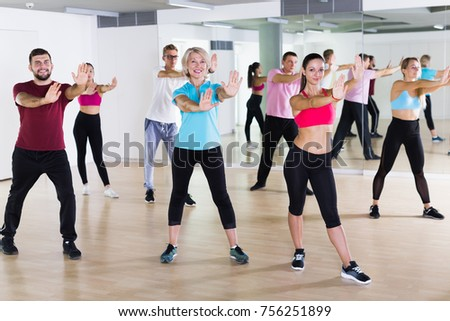 Group of positive people practicing dance in fitness studio