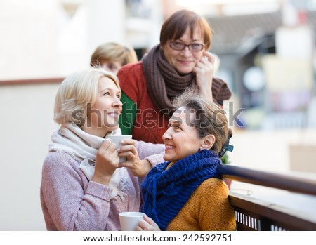 Group of positive senior female friends drinking tea at balcony - stock photo