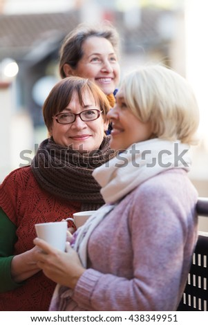 Group of positive senior females drinking tea at balcony. Focus on brunette