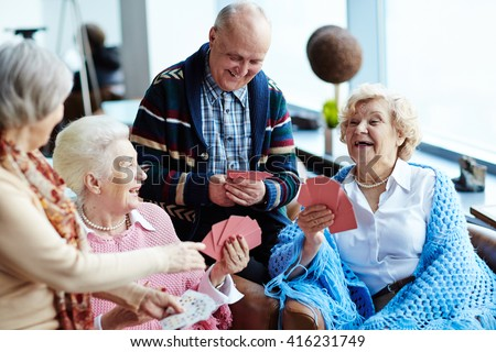 Group of positive seniors playing cards