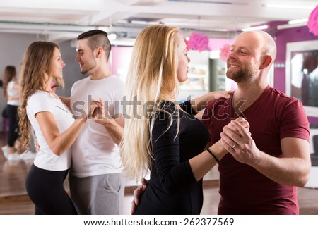 Group of positive smiling young adults dancing salsa at dance class - stock photo