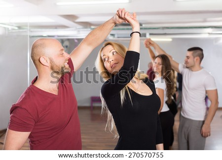Group of positive smiling young adults dancing salsa in club - stock photo