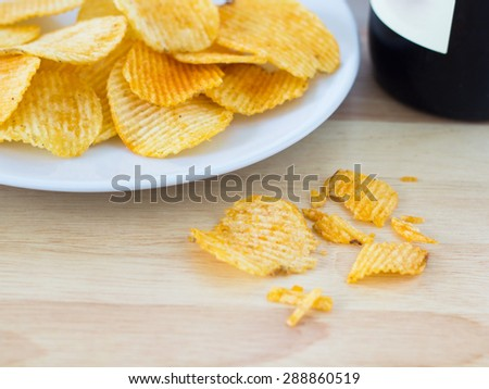 Group of potato chip on white plate and a wine bottle