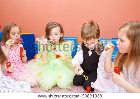 Group of preschool kids blowing bubbles at the birthday party - stock photo