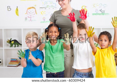 group of preschool kids with hand paint in classroom - stock photo
