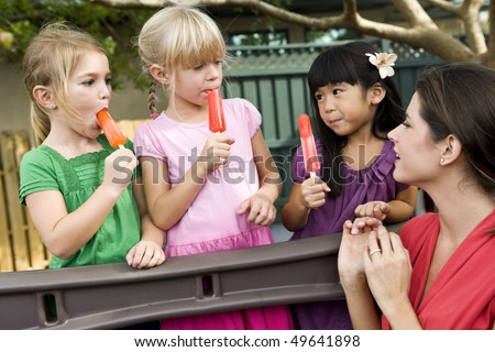 Group of preschool 5 year old girls eating popsicles in daycare with teacher