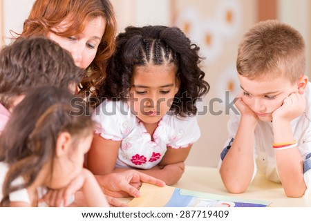 Group of preschooler with teacher in classroom. - stock photo