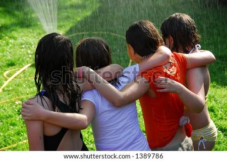 Group of preteen girls having fun outside running through sprinkler - stock photo