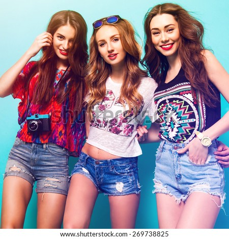Group of pretty young women's in trendy summer  clothes posing in studio against blue background. Three pretty woman smiling and wolfing together. sunny summer colors. - stock photo