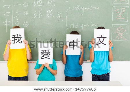 group of primary school students holding paper saying i love chinese - stock photo
