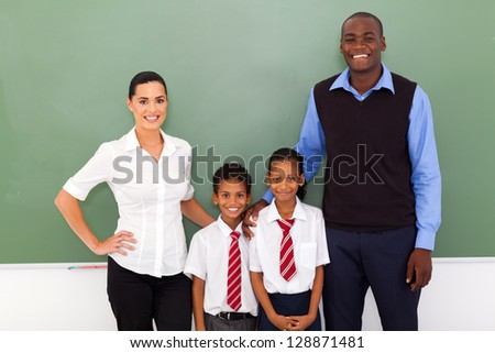 group of primary school teachers and students in classroom - stock photo