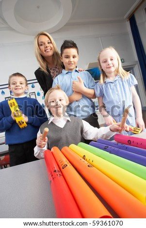 Group Of Primary Schoolchildren And Teacher Having Music Lesson In Classroom - stock photo