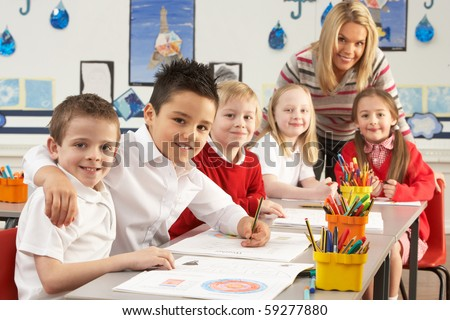 Group Of Primary Schoolchildren And Teacher Working At Desks In Classroom - stock photo