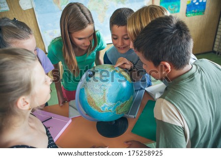 Group of primary schoolchildren around a globe in a geography lesson.