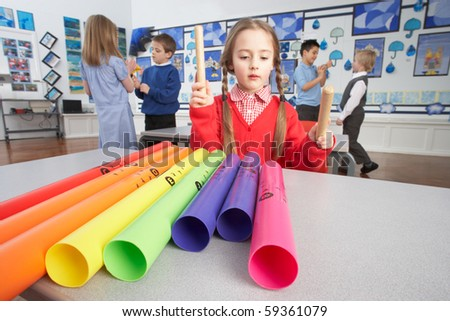 Group Of Primary Schoolchildren Having Music Lesson In Classroom - stock photo