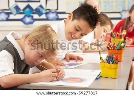 Group Of Primary Schoolchildren In Classroom Working At Desks - stock photo