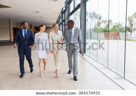 group of professional businesspeople walking in office building - stock photo