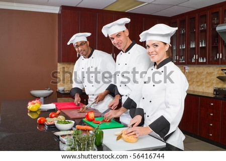 group of professional chefs cooking in commercial kitchen - stock photo