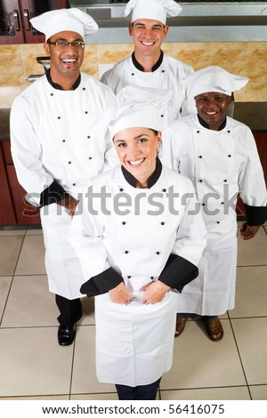 group of professional chefs in commercial kitchen - stock photo