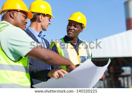group of professional construction workers and architect on site - stock photo