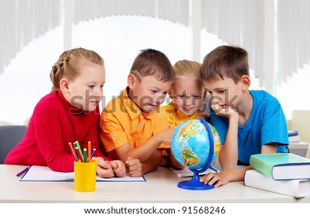 Group of pupils studying a globe together - stock photo