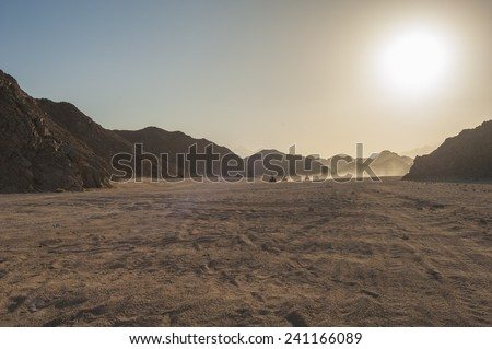 Group of quad bike atv vehicles traveling through rocky desert on safari with sunset - stock photo