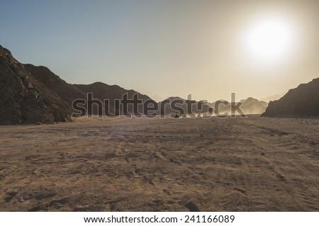 Group of quad bike atv vehicles traveling through rocky desert on safari with sunset - stock photo