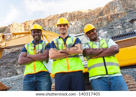 group of quarry workers standing next to excavator with arms crossed - stock photo