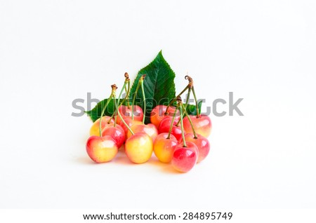 Group of Rainier cherries and leaves on white background. They are grown in Yakima Valley, a prime agricultural area of Washington State and the largest variety of crops in the Pacific Northwest.