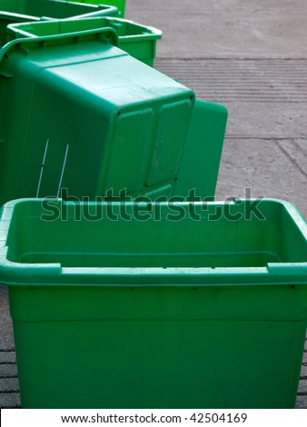 Group of recently emptied green plastic recycle bins - stock photo