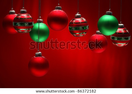 Group of red and green Christmas balls hanging over red background. - stock photo