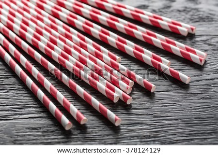 Group of red and white straws lying on a dark textured surface. There is free space on three sides around the straws. Close-up photo. Horizontal. - stock photo