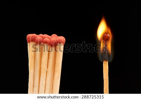 Group of red wooden matches standing with burning match, isolated on black background - stock photo