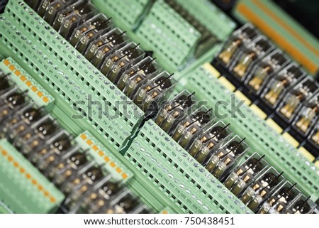 Group of relays in green sockets on DIN35 rail system