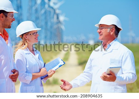 group of researchers on wind power station - stock photo
