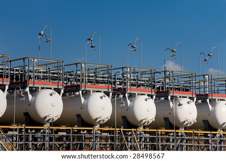 group of reservoirs for primary oil processing on blue sky background - stock photo
