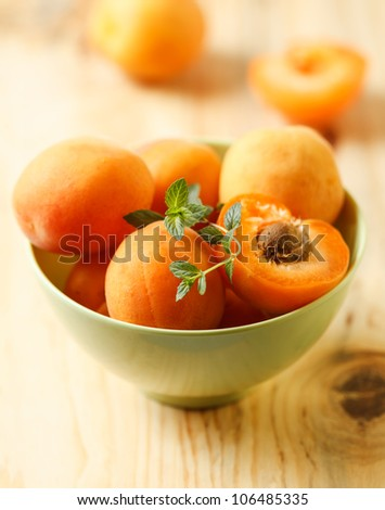 Group of ripe juicy fruit apricot on a green bowl - stock photo
