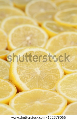 Group of ripe lemons cut in slices forming a background