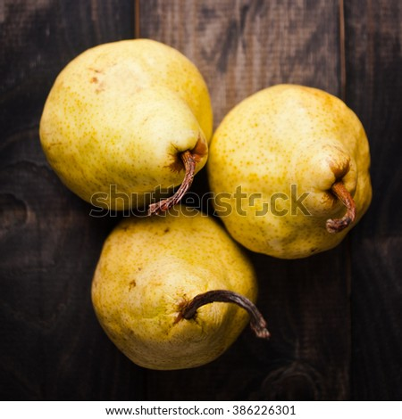 Group of ripe yellow pears on rustic background. Top view - stock photo