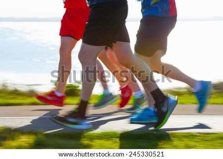 Group of runners compete in the race on coastal road. Blurred motion