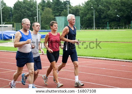 Group of running people on a race track - stock photo