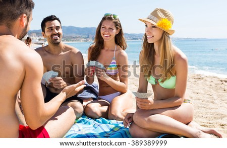 Group of russian people playing cards on summer beach