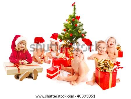 Group of Santa kids sitting beside Christmas tree - stock photo