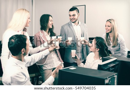Group of satisfied colleagues drinking champagne at office