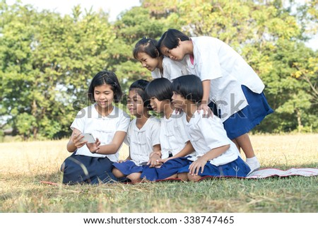 group of school kids with smartphone  taking selfie in the field