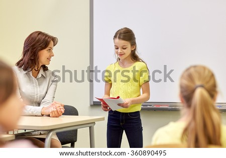 group of school kids with teacher in classroom - stock photo
