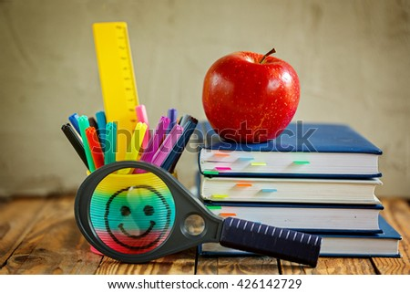 Group of school supplies and books and red apple over on background.School, stationary, equipment.